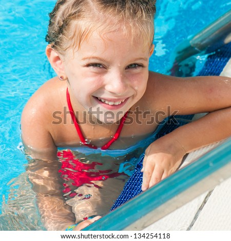 Smiling cute little girl in swimming pool - stock photo