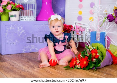 Smiling cute little girl sitting on a house floor among flowers playing  game fun