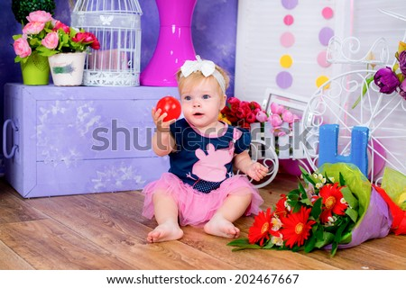 Smiling cute little girl sitting on a house floor among flowers playing with ball game