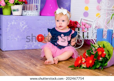 Smiling cute little girl sitting on a house floor among flowers playing with ball game fun