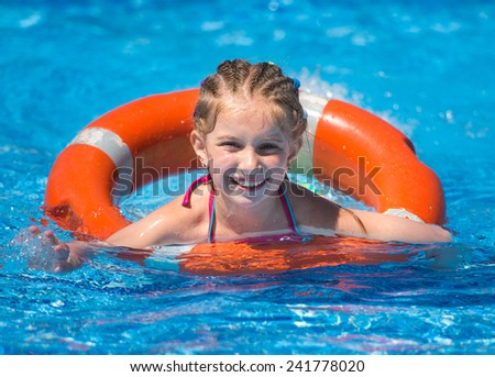 smiling cute little girl swims with a lifeline in the pool in  summer - stock photo