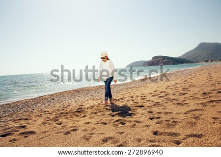 Smiling cute little girl walking on the beach. Child on vacation