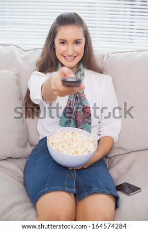 Smiling cute model on cosy sofa changing tv channel - stock photo
