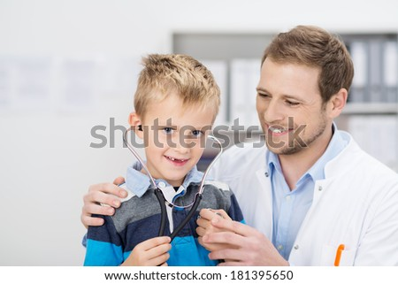 Smiling cute young blond boy in a doctors surgery sitting with the stethoscope in his ears as the friendly male physician does his examination - stock photo