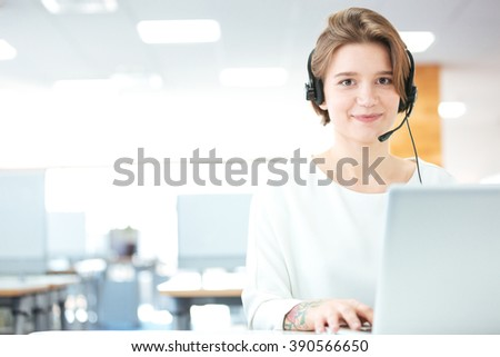 Smiling cute young woman customer support call operator in office - stock photo