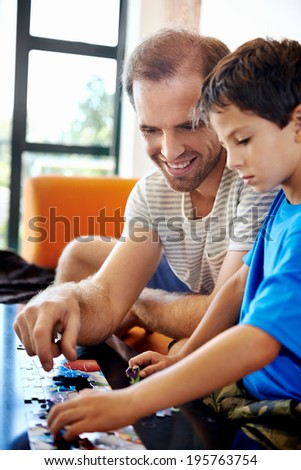 Smiling dad and son building puzzle together