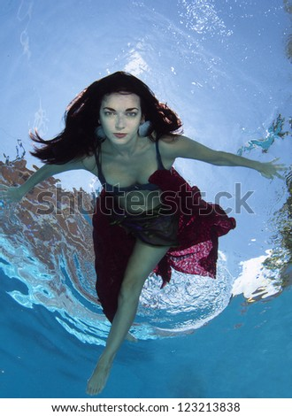 Smiling Dark Haired Model Underwater - stock photo