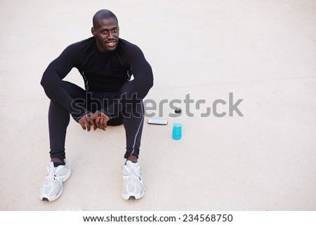 Smiling dark skinned sportsman resting sitting on the road, dark skinned runner resting after run sitting in beautiful park at evening - stock photo