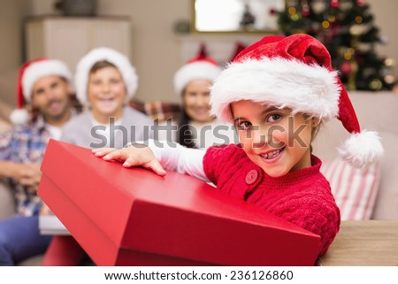 Smiling daughter holding gift with her family behind at home in the living room - stock photo