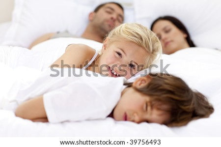 Smiling daughter relaxing with her brother and parents sleeping in bed - stock photo