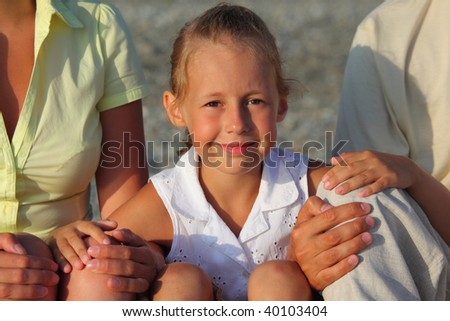 Smiling daughter sitting between parents on beach
