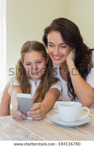 Smiling daughter with mother taking self portrait through mobile phone at table - stock photo