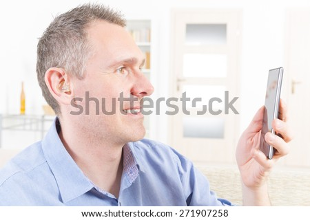 Smiling Deaf man talking using mobile phone at home - stock photo