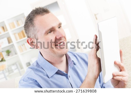Smiling Deaf man talking using tablet at home - stock photo