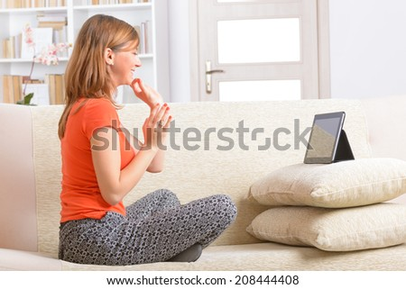 Smiling Deaf woman talking using sign language on the tablet - stock photo