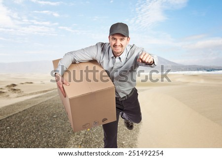 smiling delivery man and desert background - stock photo