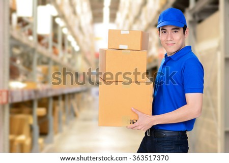 Smiling delivery man carrying boxes on blur warehouse background - stock photo