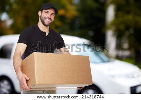 Smiling delivery man holding a paper box - stock photo