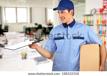 Smiling delivery man, holding clip board and carton box, inside office. - stock photo
