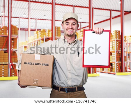 smiling delivery man in classic warehouse - stock photo