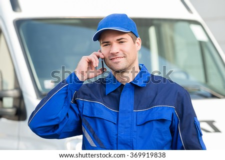 Smiling delivery man in uniform using mobile phone against truck