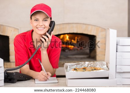 Smiling delivery young woman of pizza on the phone. The boxes of pizza on the table. - stock photo