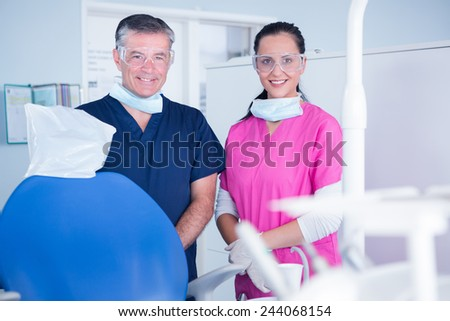 Smiling dentist and assistant with protective glasses at the dental clinic - stock photo