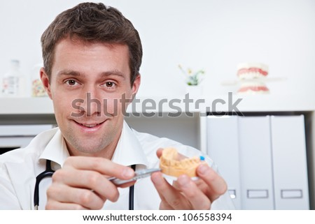 Smiling dentist in office showing dental cast - stock photo