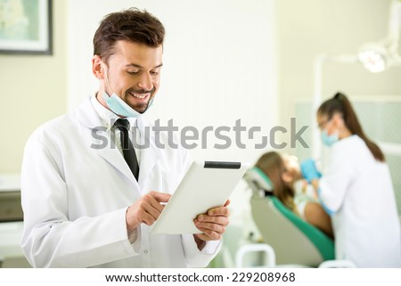 Smiling dentist with a tablet in hands. Another dentist  and patient on background. - stock photo