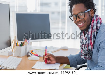Smiling designer drawing something with a red pencil in a modern office - stock photo