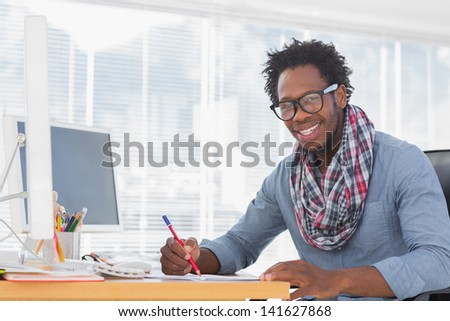 Smiling designer drawing with a red pencil on a desk in a modern office - stock photo
