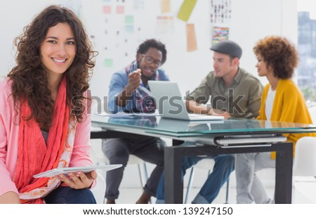 Smiling designer using tablet with team at work behind her - stock photo