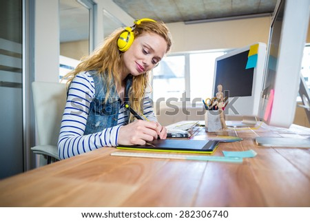 Smiling designer working with digitizer and listening music in the office - stock photo