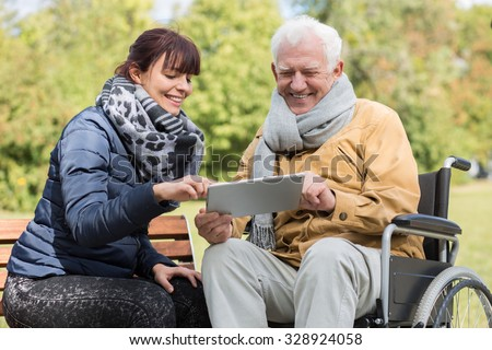 Smiling disabled man and caregiver with a tablet - stock photo