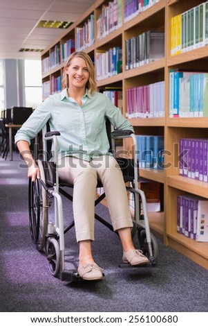 Smiling disabled student in library at the university - stock photo