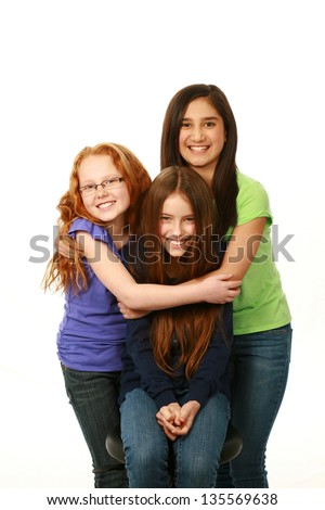 smiling diverse group of preteen girls hugging