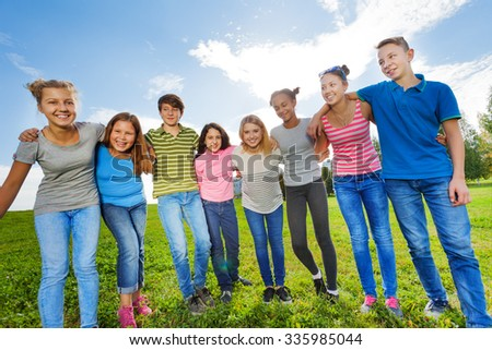 Smiling diversity friends standing on grass in row