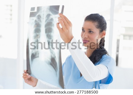 Smiling doctor analyzing xray in medical office - stock photo