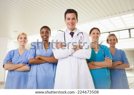 Smiling doctor and nurses with arms crossed wearing breast cancer awareness ribbon - stock photo