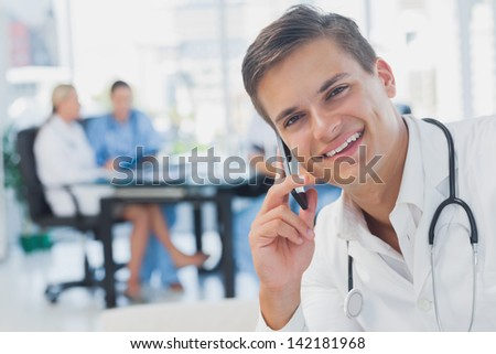 Smiling doctor calling while his colleagues are in a meeting - stock photo