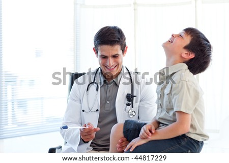 Smiling doctor checking a child's reflex during a medical visit