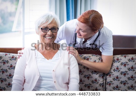 Smiling doctor consoling senior woman at home