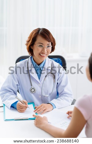 Smiling doctor filling medical report for her patient - stock photo