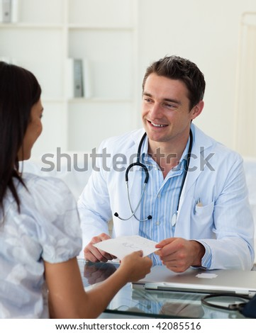 Smiling doctor giving a prescription to his female patient during a visit - stock photo