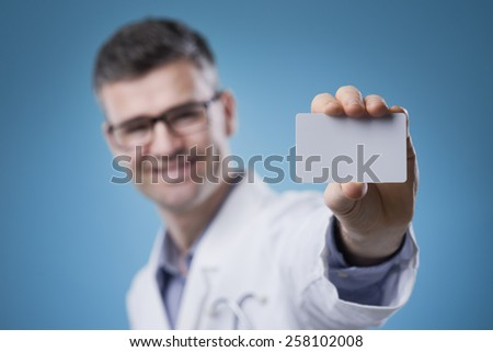 Smiling doctor holding a blank business card - stock photo