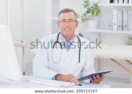 Smiling doctor looking at camera with clipboard in medical office