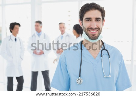Smiling doctor looking at camera with co-workers behind him