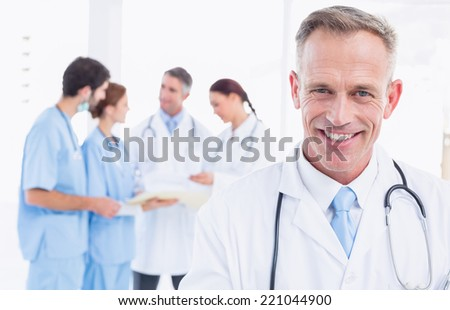 Smiling doctor looking at camera with co-workers behind him - stock photo