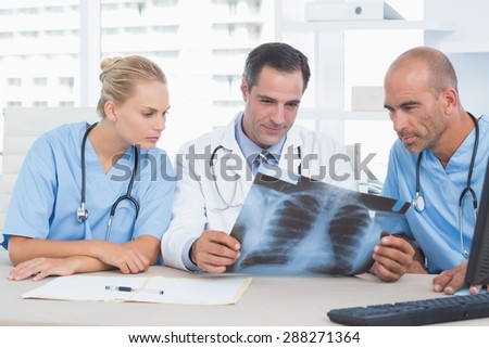 Smiling doctor looking at Xray with his colleagues in medical office - stock photo