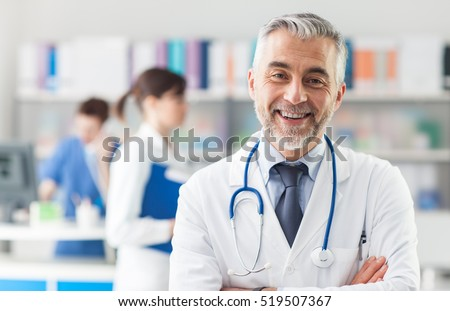 Smiling doctor posing with arms crossed in the office, he is wearing a stethoscope, medical staff on the background